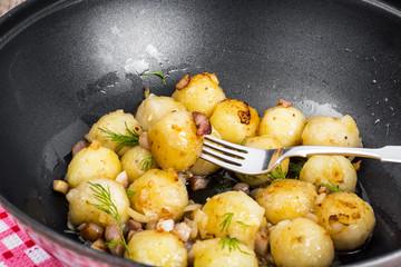 Fried potato dumplings with bacon in frying pan