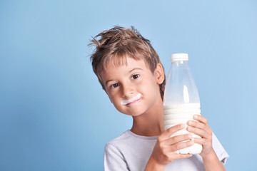 Cute kid holding plastic bottle of milk on blue background