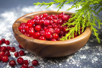 Fresh cranberries in a wooden plate on a dark background, and near the green branches