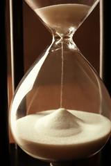 Black hourglass with white sand, closeup
