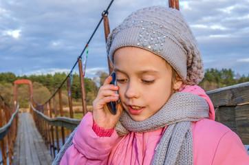 Девочка звонит по мобильному телефону стоя на подвесном мосту.