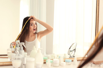 Young woman measuring hair length in front of mirror at home
