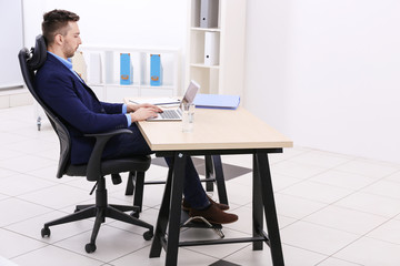 Handsome young man working with laptop in office. Incorrect posture concept