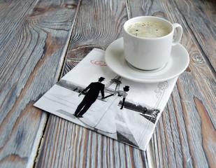 Чашка с кофе и салфетка с символом Парижа   лежат на деревянном столе