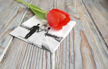 Красный тюльпан и салфетка с символом Парижа   лежат на деревянном столе