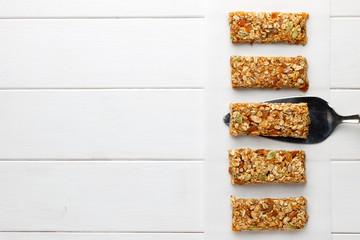Homemade no bake granola bars on white wooden background.