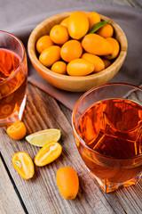 orange kumquat  liqueur in the  glasses on the wooden rustic  table