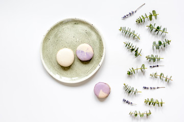 Trendy design with macaroons on plate, eucalyptus and lavander top view