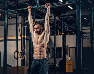 A man doing ABS workouts on pull up bar in a gym club.