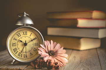 Roman Numeral in Vintage Alarm Clock and Stack of Book Background with Copy Space for Advertise or Web Promote about the Time or Nostalgia Concept