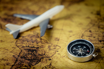 Retro Compass with toy airplane on Vintage world map for explorer concept
