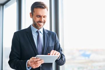 Happy businessman using digital tablet standing in office