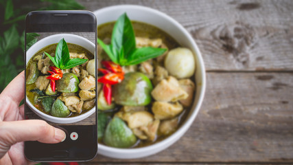 Taking a photo by Finger Pressing on Smartphone for Photograph Thai Chicken Green Curry. Image for Food Advertise or Social Media with Food Concept