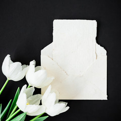 Paper envelope and cards and tulips flowers on black background. Flat lay, top view. Vintage background