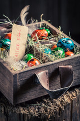 Farm eggs for Easter in the wooden box with hay