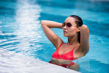 Woman wearing red swimsuit and sunglasses sitting in swimming pool, touching wet hair