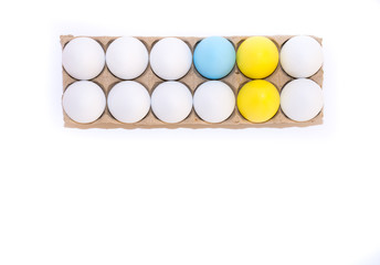 Two Easter eggs dyed yellow, one dyed blue and nine white hard boiled hen's eggs in a cardboard carton photographed from above against a white background with copy space.