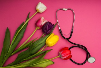 Stethoscope and colorful tulips on a pink background.
