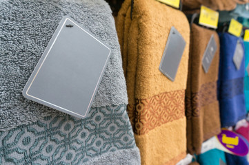 Colorful towels with Blank Label on shelf of rack background