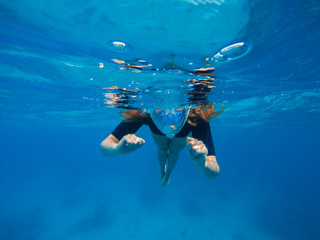 Woman swimming in blue water. Beautiful woman under water before dive to coral reef.