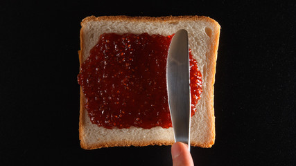 TOP VIEW: Human hand spreads a raspberry jam on a bread