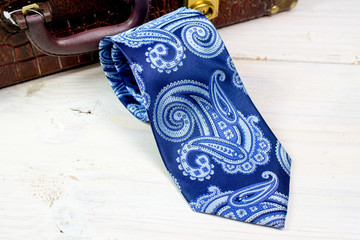 Paisley design blue tie in front of vintage suitcase