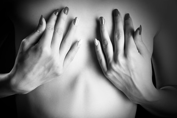 female hands covering small breasts closeup monochrome