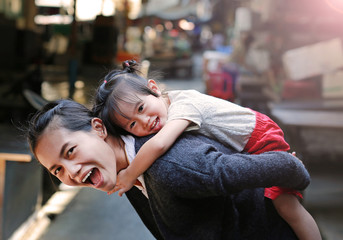 Happy family, Portrait of cute little girl riding on mother back in Bangkok Thailand.