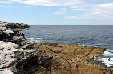 Sydney, Australia - Feb 5, 2017. People relaxing on the rocks of Ray O'Keefe Reserve, North Bondi.