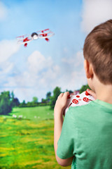 Happy boy drives toy quadcopter drone at nature landscape