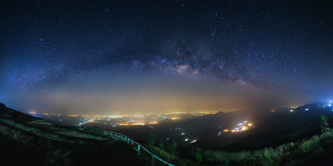 Panorama milky way galaxy and city light at Phutabberk Phetchabun in Thailand.Long exposure photograph.With grain