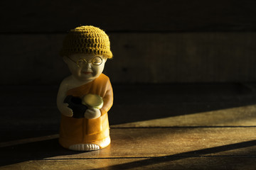 Novice doll stucco in dim light on wooden table