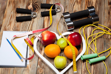 White heart, apples and oranges, diet, healthy , dumbbells  a jump rope on  wooden background