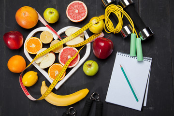 Diet plan, fruits and centimeter on a black background