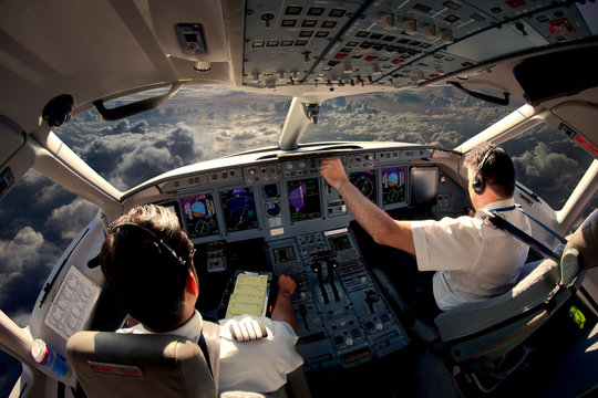 Flight Deck of modern passenger jet aircraft. Pilots at work. Cloudy sky and sunset view from the airplane cockpit.
