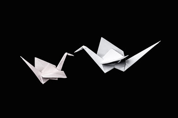 Origami cranes isolated on black background