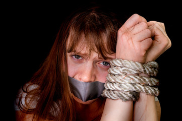 Tied rope hands of abused woman isolated on black