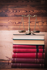 golden scale on top of stack of law books