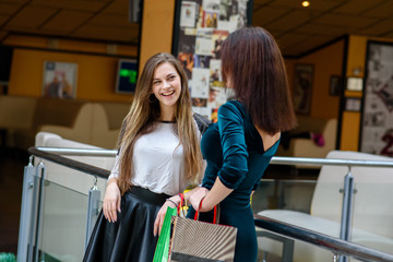 Two happy girls talking in the mall.