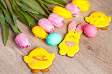 Easter composition of the branches,Easter bunny, cakes, tulips colored eggs cooked for the holiday on the wooden background