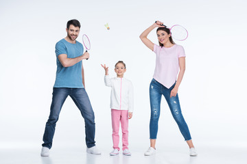 smiling family with badminton rackets and shuttlecock on white