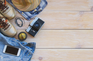 Essential travel items:clothing, smart phone, mini globe and vintage camera on wooden background. Casual traveler's outfits with blue jeans, hat, check shirt, gold sneakers and bracelets.