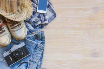 Essential travel items:clothing, smart phone,  and vintage camera on wooden background. Casual traveler's outfits with  blue jeans, hat, check shirt and gold sneakers. Ready to take a trip concept.