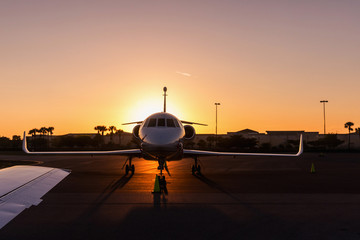 Modern Jet parked on runway in sunny day, amazing sunset.