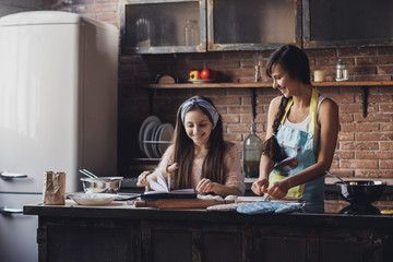 Young woman with her little sister cooking holiday pie