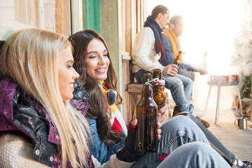 side view of cheerful friends drinking beer on barbecue
