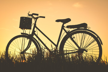 Garden Poster Bicycle Silhouette of old bicycle on grass with the sky sunset, color of vintage tone and soft focus concept journey
