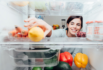 Woman taking a lemon out of the fridge