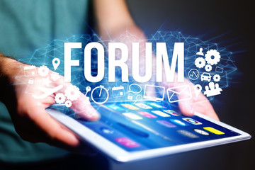 Concept of man holding futuristic interface with forum title and multimedia icons flying all around - Internet concept
