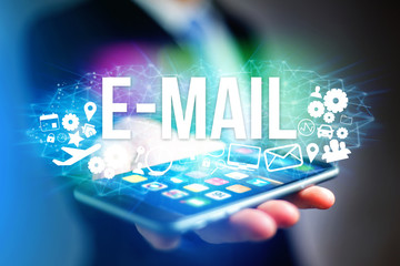 Concept of man holding futuristic interface with e-mail title and multimedia icons flying all around - Internet concept